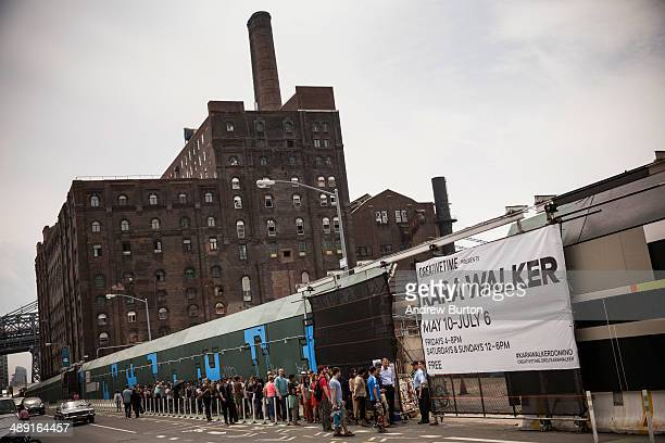 People wait outside to see Kara Walker's A Subtlety a seventyfive and a half feet long and thirtyfive and a half feet tall sphinx made in part of...