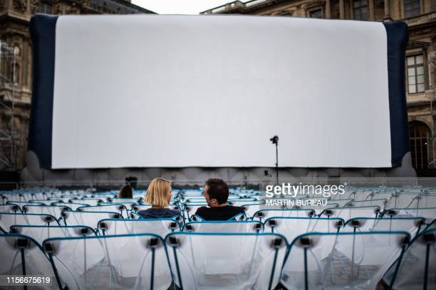 People wait prior to the screening of the movie La Reine Margot at the Louvre Museum the first of eight screenings of the outdoor cinema Cinema...