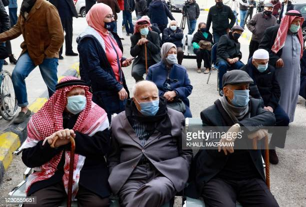 People wait their turn to receive a dose of vaccine against the coronavirus COVID-19 disease, outside a vaccination centre in the Jordanian capital...
