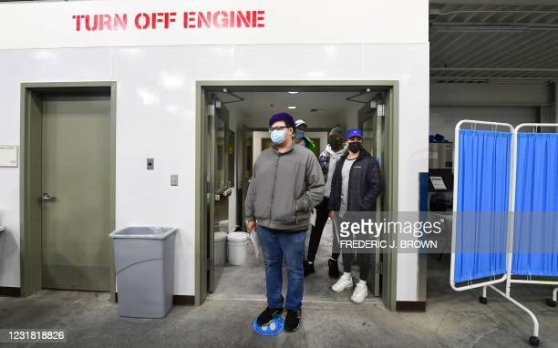 People wait their turn to receive the Pfizer Covid-19 vaccine at the Blood Bank of Alaska in Anchorage on March 19, 2021. - Alaska became the first...