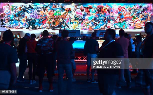 People wait their turn which can involve hours to play Nintendo Switch games as Nintendo characters are displayed on a screen at the 24th Electronic...