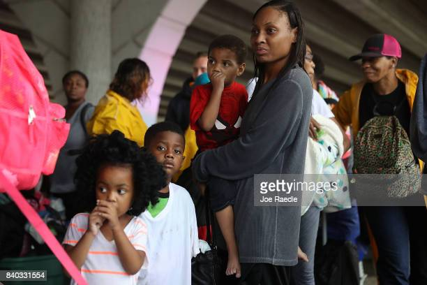 People wait to be bussed to a shelter after being evacuated from their homes by flooding from Hurricane Harvey on August 28 2017 in Houston Texas...
