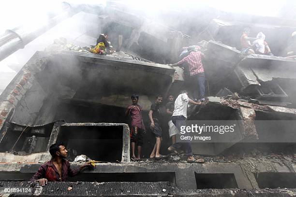 People wait to be rescued amongst the smoke at a fire which has broken out at a garment packaging factory in the Tongi industrial area on September...