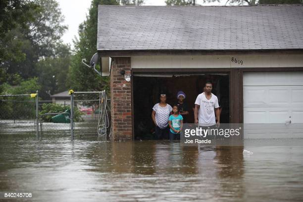 People wait to be rescued from their flooded homes after the area was inundated with flooding from Hurricane Harvey on August 28 2017 in Houston...
