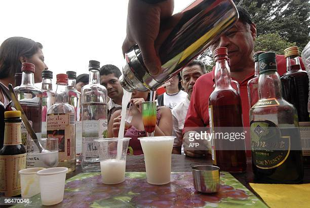 People wait to be served pisco sour a Peruvian traditional cocktail during the celebration of the Pisco Sour Day in Lima on February 6 2010 Peruvians...