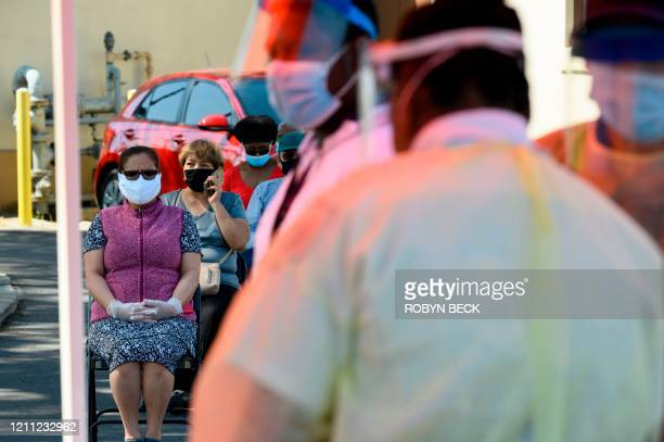 People wait to be tested for COVID19 at a mobile testing station in a public school parking area in Compton California just south of Los Angeles on...