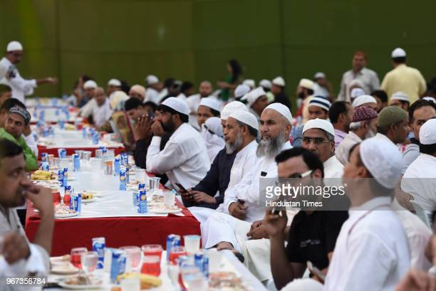 People wait to break their fast during an Iftar party organised by Delhi Chief Minister Arvind Kejriwal at Palika Services Officer's Institute at...