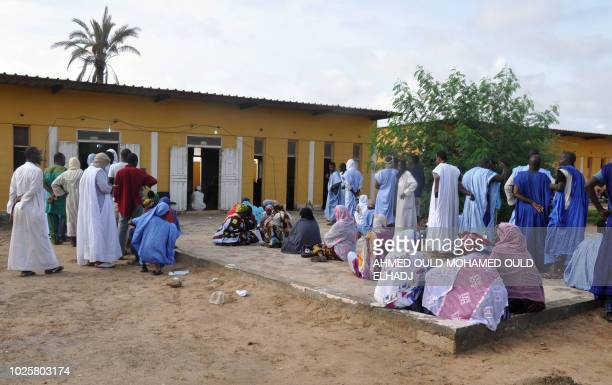 People wait to cast their vote on September 1 2018 outside a polling station in Nouakchott for the country's legislative regional and local elections...