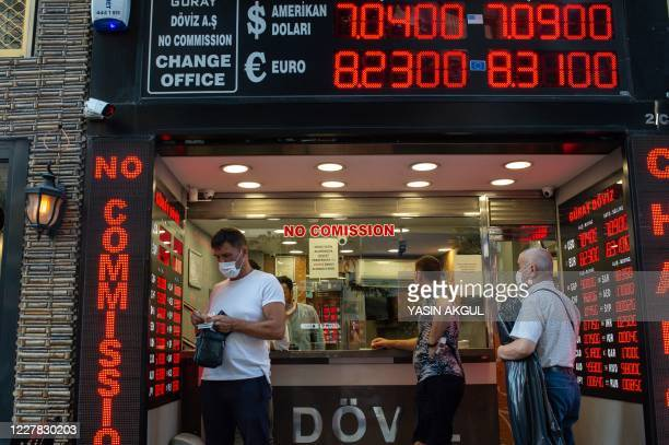 People wait to change money at an exchange office in Istanbul, on July 29, 2020. - According to reports, the Turkish Lira fell to a fresh record low...