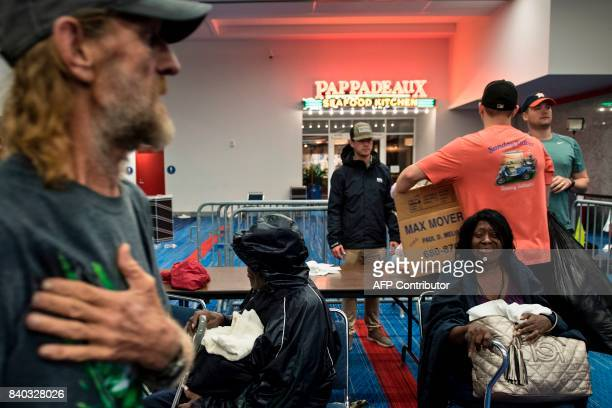 People wait to check into a shelter in the George R Brown Convention Center during the aftermath of Hurricane Harvey on August 28 2017 in Houston...