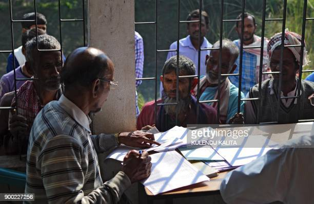 People wait to check their names on the first draft of the National Register of Citizens at Goroimari of Kamrup district in the Indian state of Assam...