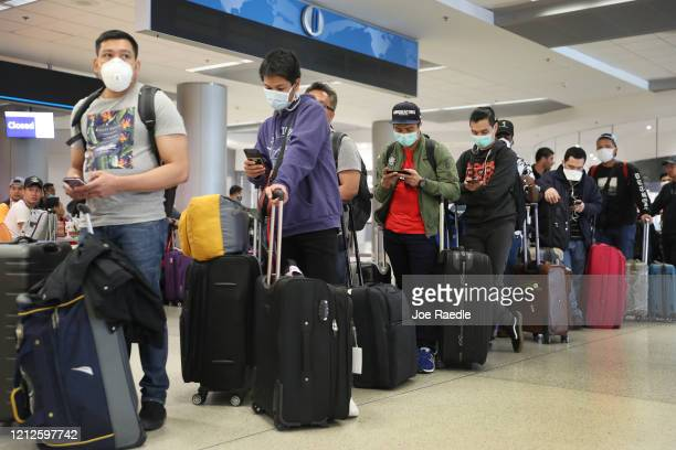 People wait to checkin at the Qatar Airways counter amid coronavirus fears at Miami International Airport on March 15 2020 in Miami Florida Airline...