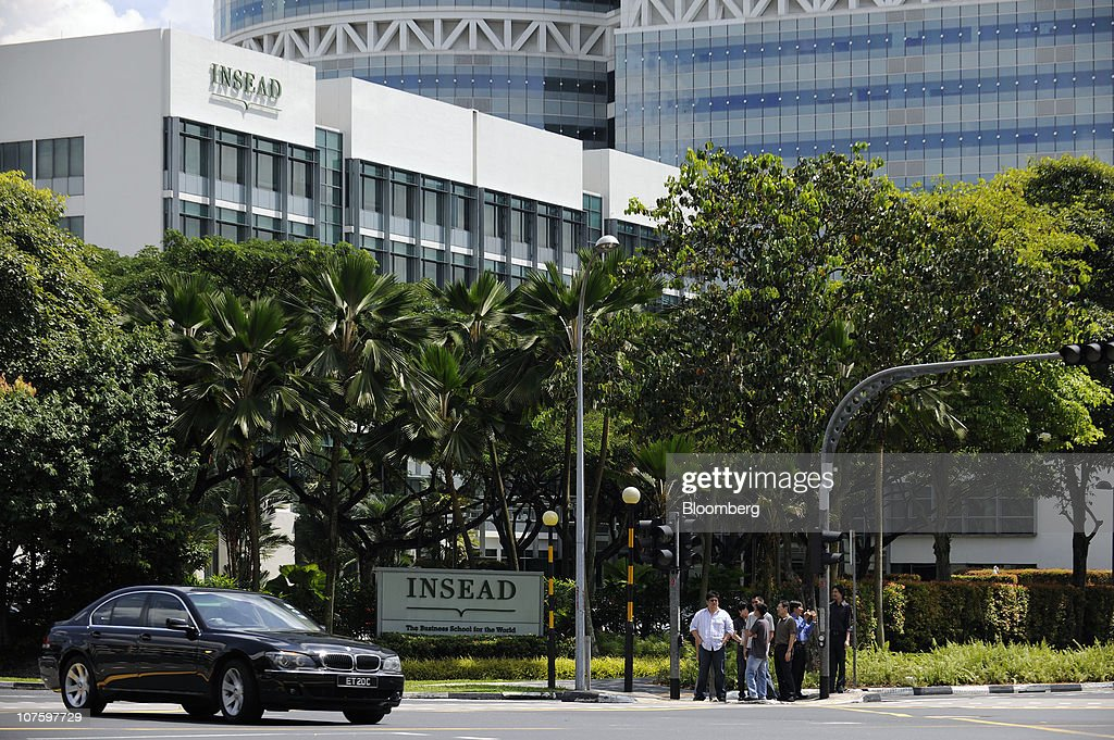 People wait to cross an intersection in front of the Asia campus of Insead in Singapore, on Monday, Dec. 6, 2010. Yale University may join Duke University, the University of Chicago, Imperial College London and France's Insead among colleges to set up a campus in Singapore, a nation of 5 million people with a land mass smaller than New York City. The city-state wants to attract 150,000 international students by 2015 as it seeks to boost the contribution education makes to gross domestic product to 5 percent from 3.2 percent last year and 1.9 percent in 2000. Photographer: Munshi Ahmed/Bloomberg via Getty Images