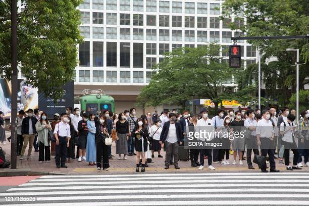 People wait to cross the road while wearing face masks as a preventive measure during the lifting of the state of emergency. Japan has lifted a state...
