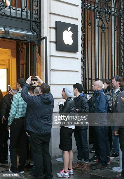 People wait to enter an Apple store on the day of the official launch of the iPhone 6s on September 25 2015 in Paris AFP PHOTO/JACQUES DEMARTHON