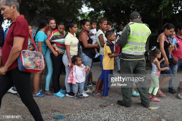 People wait to enter the Divine Providence House a churchrun charity that helps Venezuelan migrants with food and basic medical needs on March 2 2019...