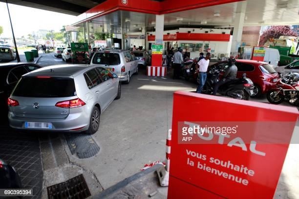 People wait to fill their tanks at a gas station on May 31 2017 in IssylesMoulineaux outside Paris as truck drivers transporting dangerous materials...