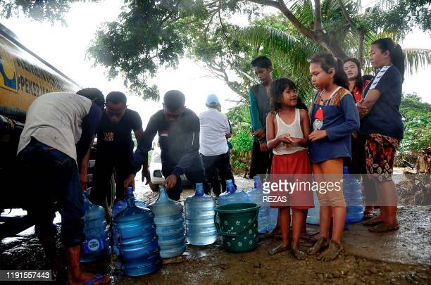 People wait to get fresh water from a truck in their flood affected village in Bekasi West Java on January 4 2020 Tens of thousands of Indonesians...