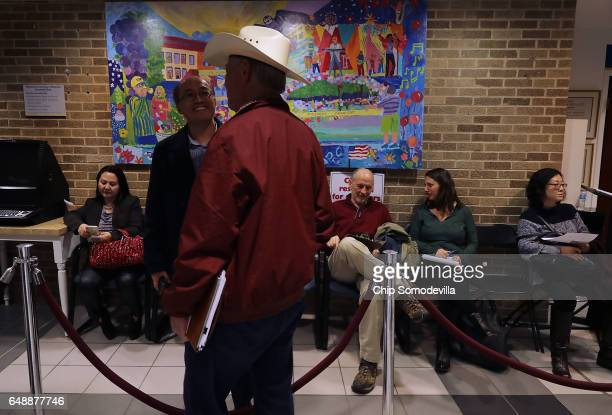 People wait to give testimony at a hearing about a propsal to become a 'sanctuary city' at City Hall March 6 2017 in Rockville Maryland While...