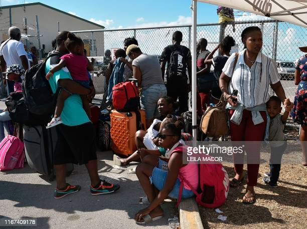 People wait to have their documents checked by airport workers so they can fly to the United States at the airport at Freeport on Grand Bahama island...