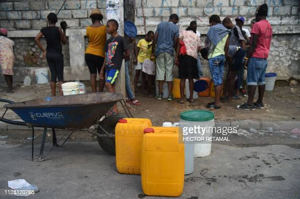 People wait to load water cans in PortauPrince on February 15 on the ninth day of protests against Haitian President Jovenel Moise and the misuse of...