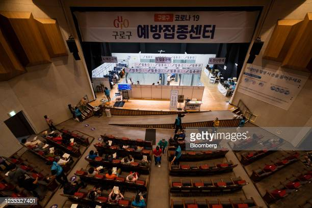 People wait to receive a dose of the Pfizer-BioNTech Covid-19 vaccine at a vaccination site inside the Guro Arts Valley Theater in the Guro district...
