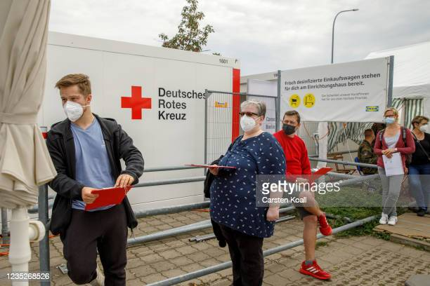People wait to receive a dose of the the Moderna vaccine in a drive-in vaccination station in an IKEA car park on the third day of the...