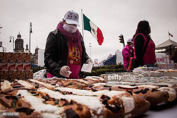 People wait to receive a slice of traditional Rosca de Reyes which is distributed to celebrate the Epiphany commemorating the arrival of the three...