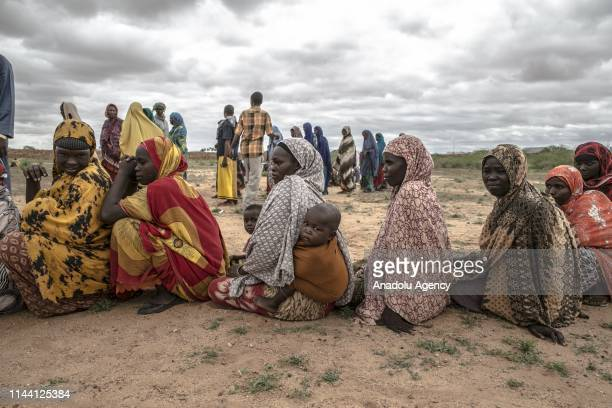 People wait to receive food aid containing rice, sugar, flour and oil distributed by Turkiye at Kasaba and Qasali refugee camps in Doolow town of...