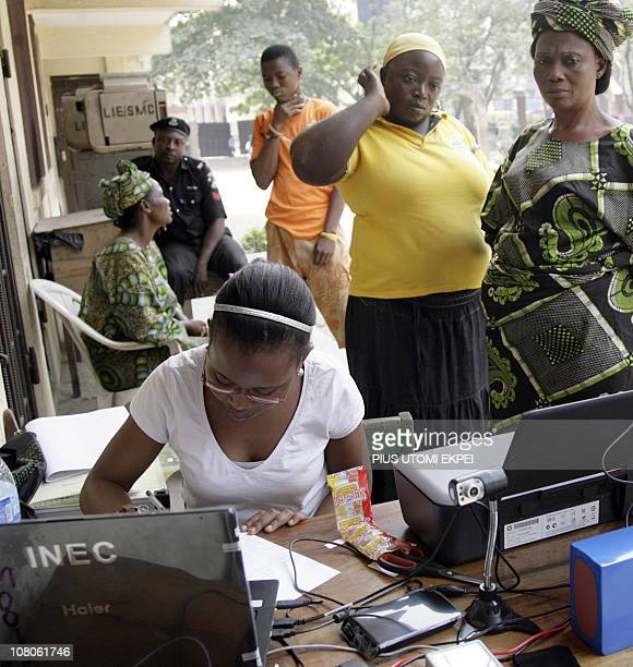 People wait to register as a female INEC official records data in a laptop during a voters registration exercise in Lagos on January 15 2011 The...