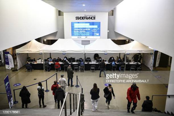 People wait to register before beeing vaccinated against Covid-19 at a vaccination centre set in the Stade de France in Saint-Denis, a northern Paris...