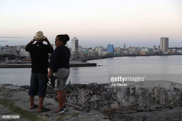 People wait to see the convoy of vehicles escorting the remains of former President of Cuba Fidel Castro pass by along the malecon off in the...