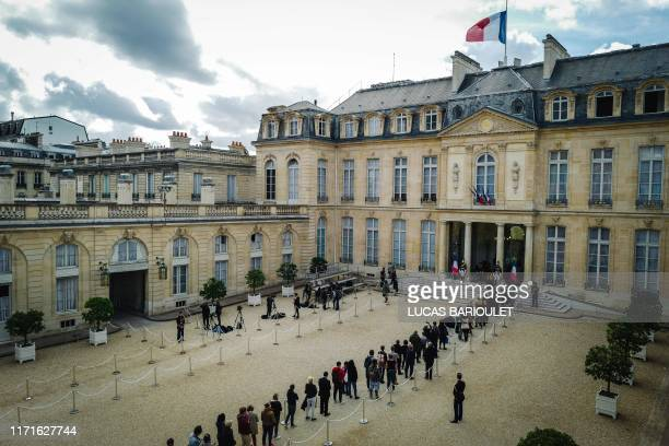 TOPSHOT People wait to sign a condolence registers for late former French President Jacques Chirac at the Elysee presidential palace in Paris on...