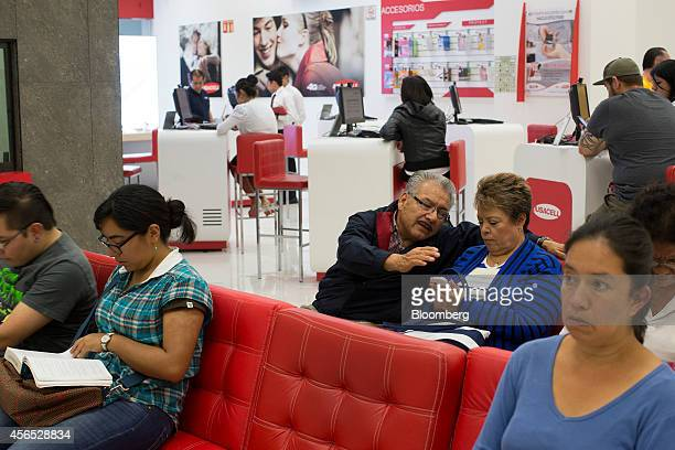 People wait to speak to customer service representatives at a Grupo Iusacell SA customer service center in Mexico City Mexico on Wednesday Oct 1 2014...
