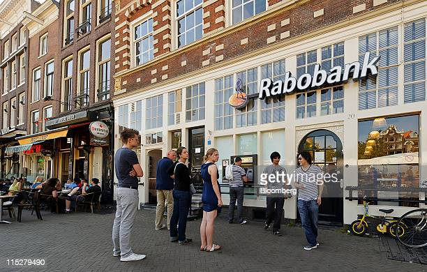 People wait to use an automated teller machine at a branch of a Rabobank Groep NV bank in in Amsterdam Netherlands on Friday June 3 2011 The Dutch...