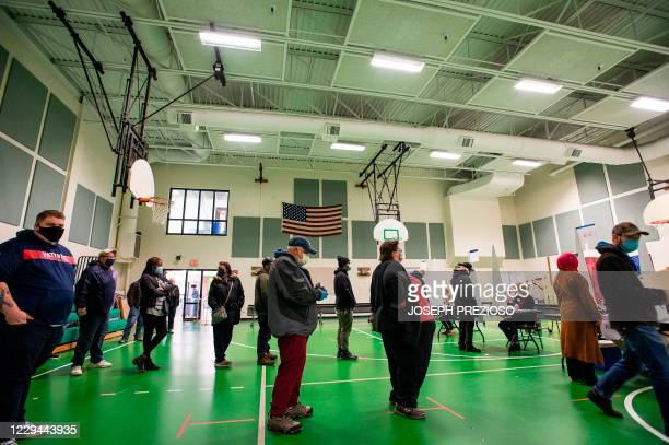 People wait to vote at a polling station in Manchester, New Hampshire, on November 3, 2020. - Americans were voting on Tuesday under the shadow of a...