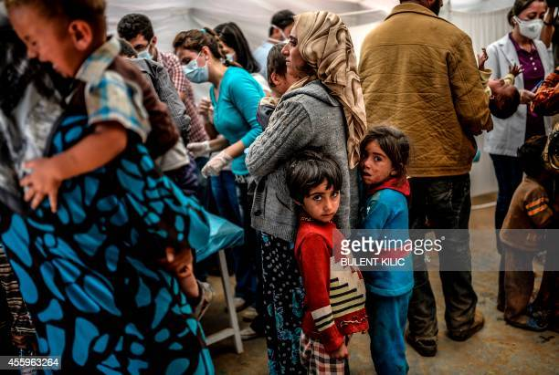 People wait with their children for vaccination at the southeastern town of Suruc in Sanliurfa province on September 23, 2014. The UN refugee agency...