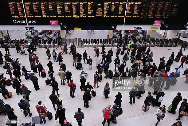 People wait with their luggage by the departure boards in Waterloo train station in central London as disruption to rail services continues on...