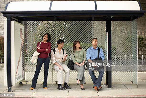 people waiting at bus stop - waiting stock pictures, royalty-free photos & images