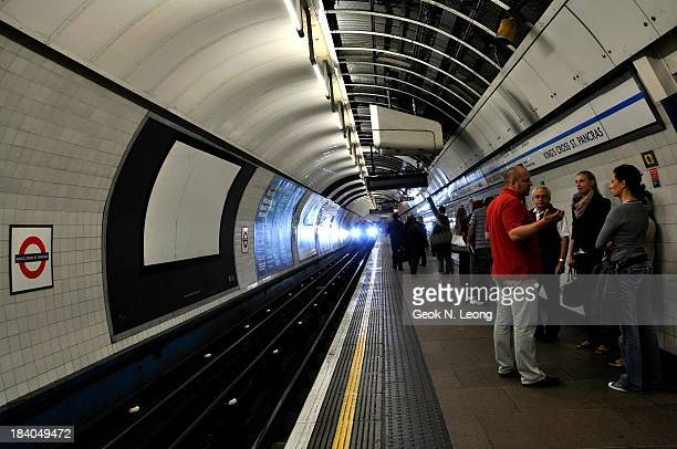 People waiting at platform with train approaching with headlights on, at Kings Cross St Pancras underground tube station in London, UK. Perspective,...