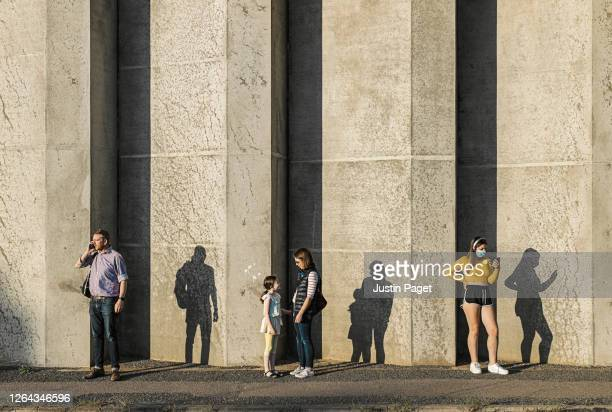 people waiting by concrete wall. they are socially distancing - four people stock pictures, royalty-free photos & images