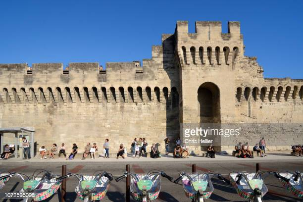 people waiting for a bus outside the medieval ramparts avignon - human powered vehicle fotografías e imágenes de stock