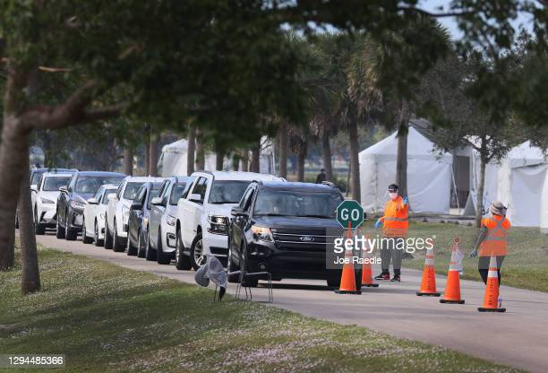 People waiting for a COVID-19 vaccine wait in their cars as workers for the Florida Department of Health in Broward direct cars at the drive-thru...