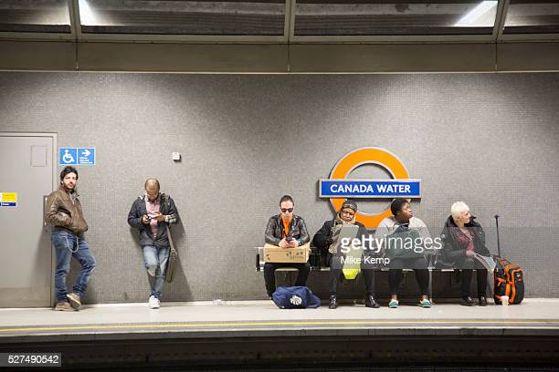 People waiting for a London Overground train on the platform at Canada Water station London UK