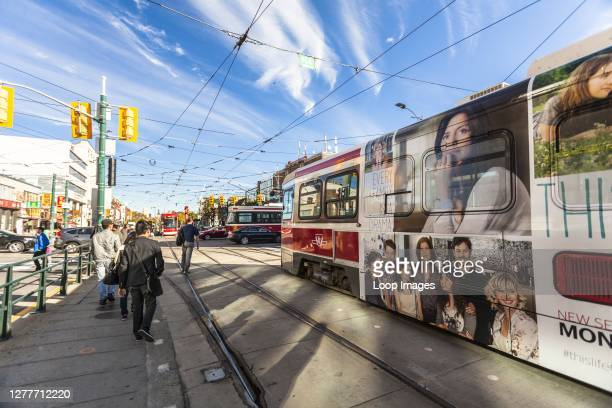 People waiting for a tram to pass on the busy streets of Chinatown in Toronto in Canada.