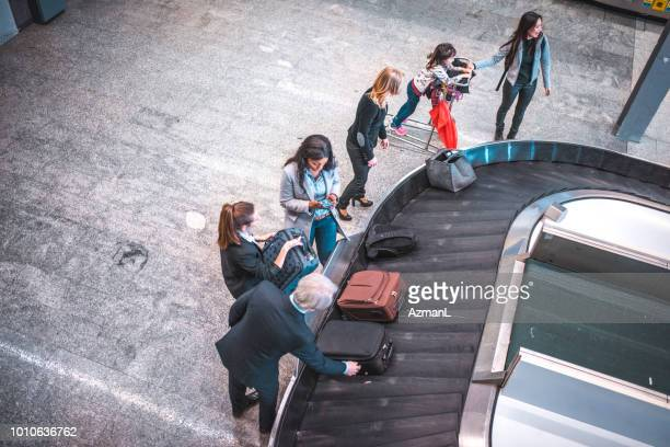 people waiting for baggage at airport terminal - baggage claim stock pictures, royalty-free photos & images