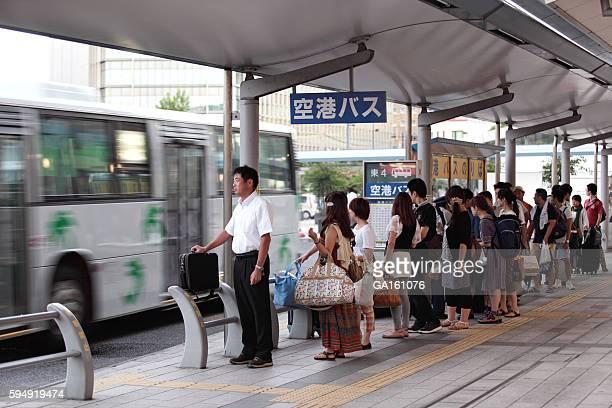 Leute warten auf den bus zum Flughafen
