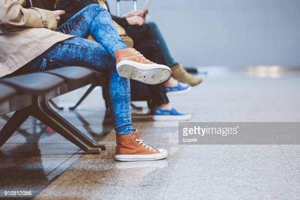 People waiting for flight in airport lounge, close up of legs