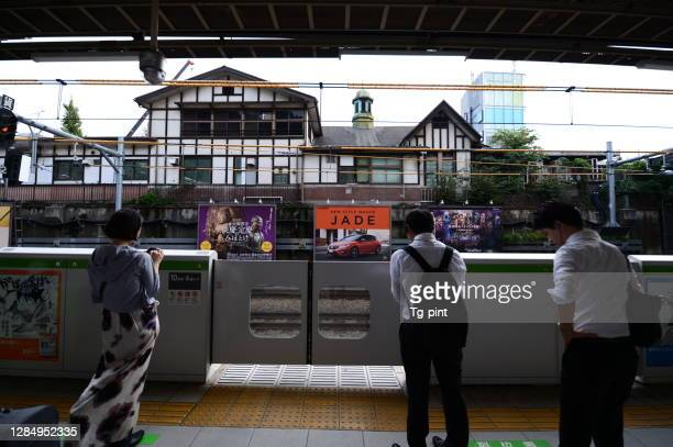 people waiting for the train at the platform of harajuku station - safety american football player stock pictures, royalty-free photos & images