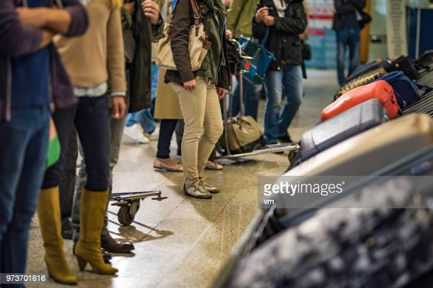 people waiting for their luggage at an airport - baggage claim stock pictures, royalty-free photos & images